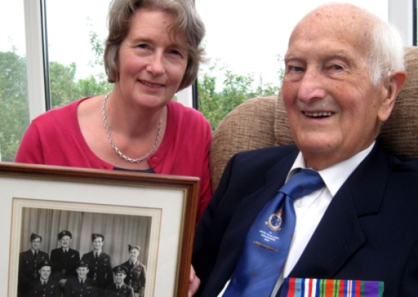 Mr Norman Allen, veteran of Bomber Command during WW2, with his daughter Mrs Janet Kells, who is holding a picture of his Lancaster crew - the young airman is second left back row. They were in London yesterday - along with his daughter-in-law Mrs Margaret Allen - to see the Queen unveil the £7m Memorial to the 55,000 men of Bomber Command who died during the raids on Germany. INPT27-950.