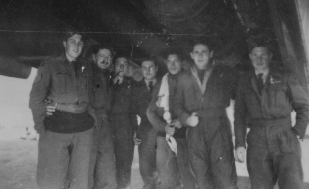 The Elmslie crew showing off the size of the Lancaster's bomb bay, Mepal, October 1944. Left to Right: Alan Wiltshire (Nav), Gordon Burberry (M/UG), Peter Dear (W/Op), Ken Futter (F/E), Jim McKenzie (B/A), John Vallender (RG), Jim Elmslie (Pilot). Photo from Alan Wiltshire, courtesy of NZ Bomber Command Association archives.